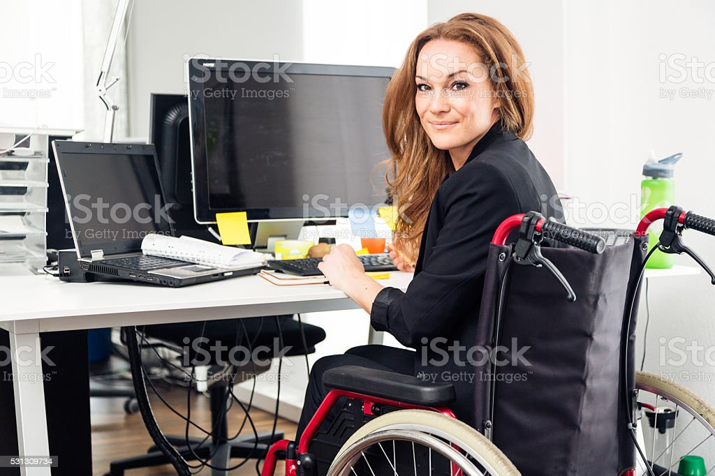 woman sitting in wheelchair working in modern office stock photo