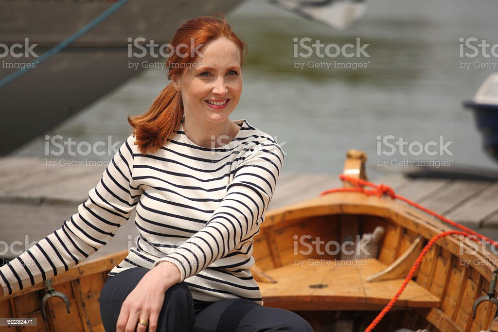 Woman sitting in wooden rowboat royalty-free stock photo