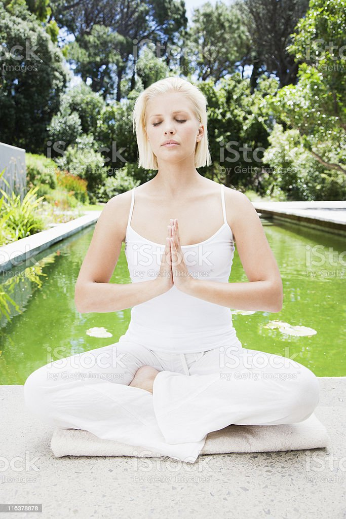 Woman sitting in yoga pose next to pond royalty-free stock photo
