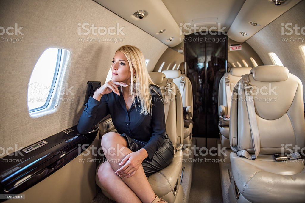 Woman sitting inside private airplane stock photo