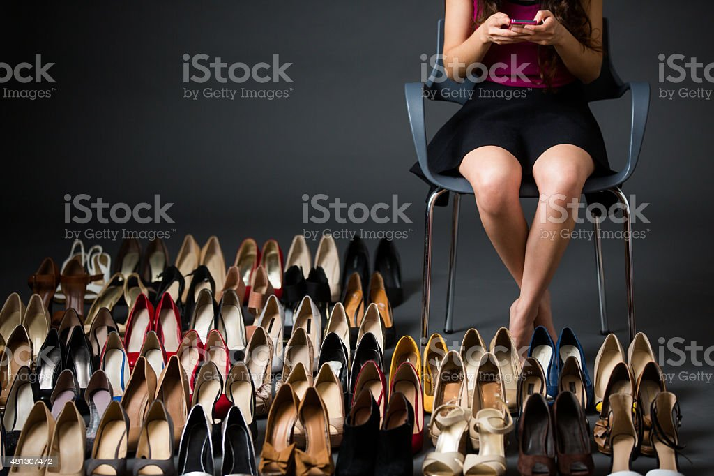 Woman sitting near high heels and text messaging stock photo