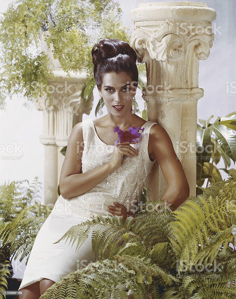Woman sitting near pedestal and pot plants, portrait royalty-free stock photo