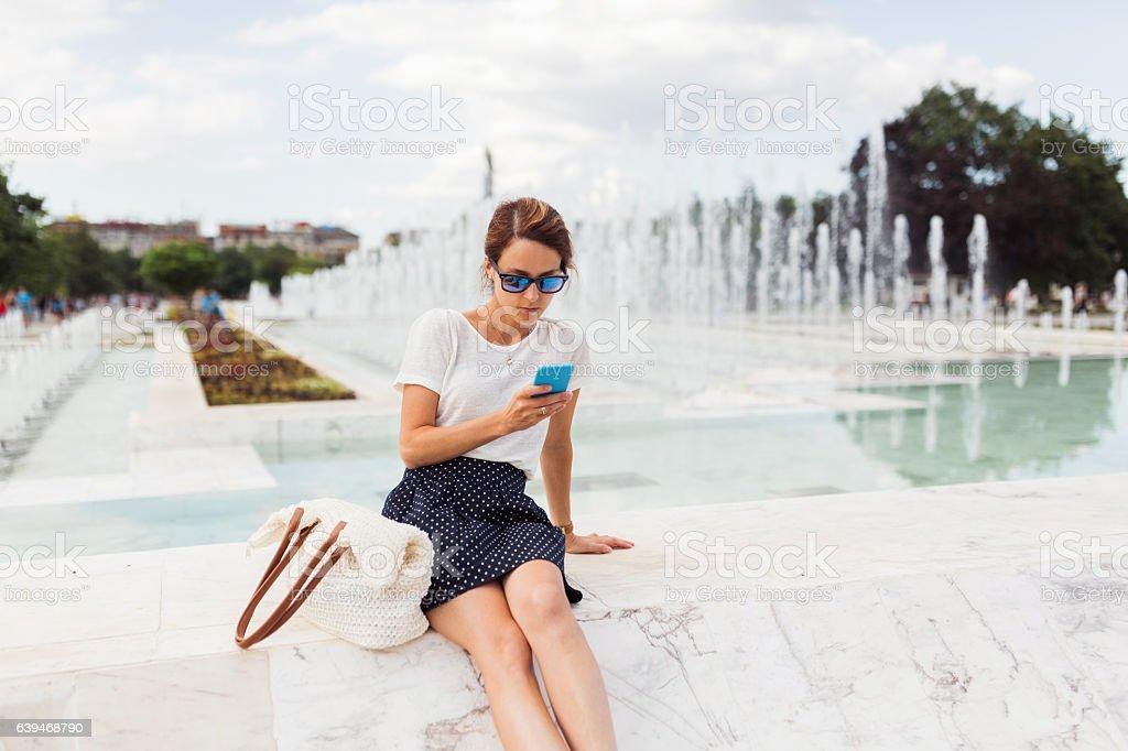 Woman sitting near the fountain stock photo