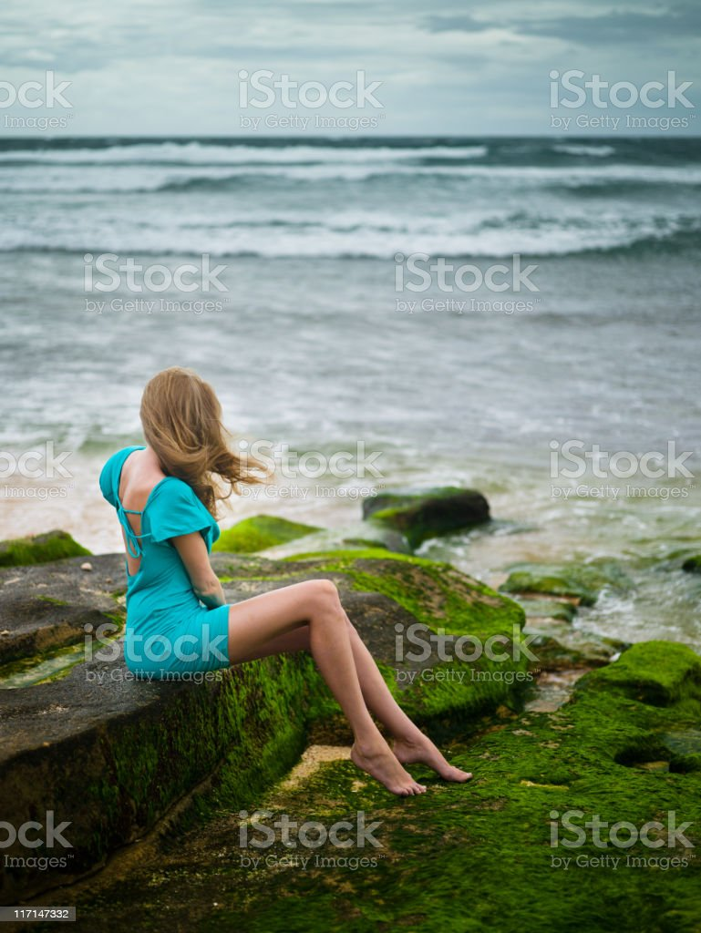 Woman sitting near the ocean royalty-free stock photo