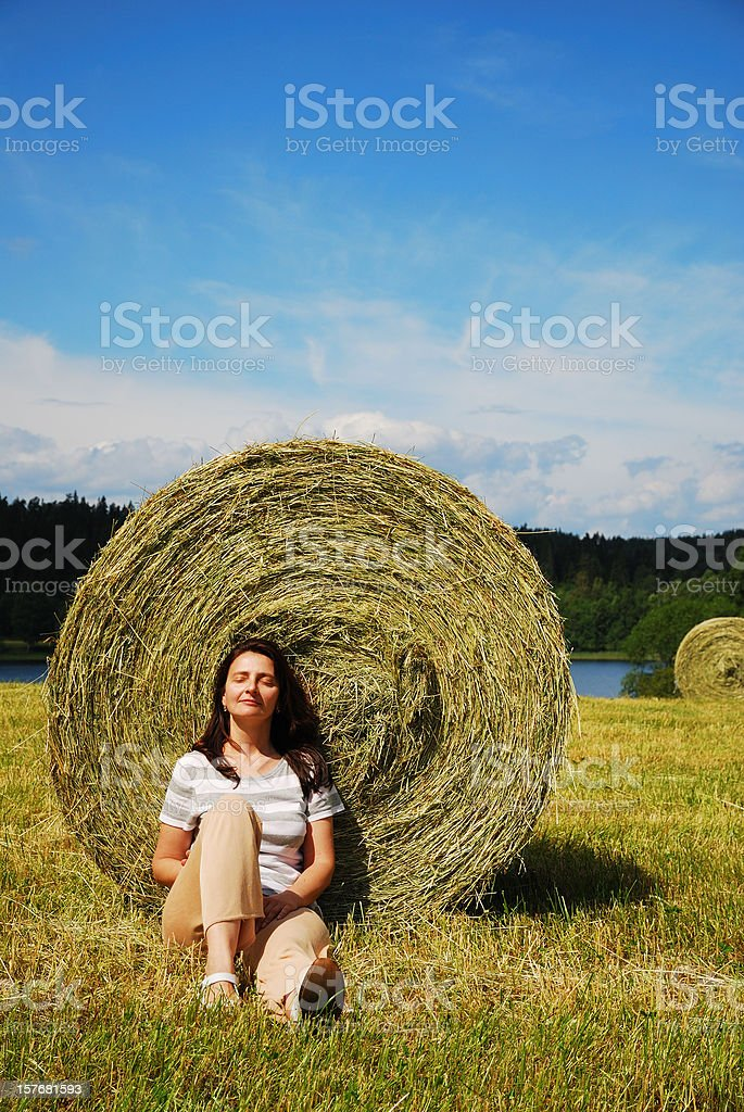 Woman sitting near the straw bale royalty-free stock photo