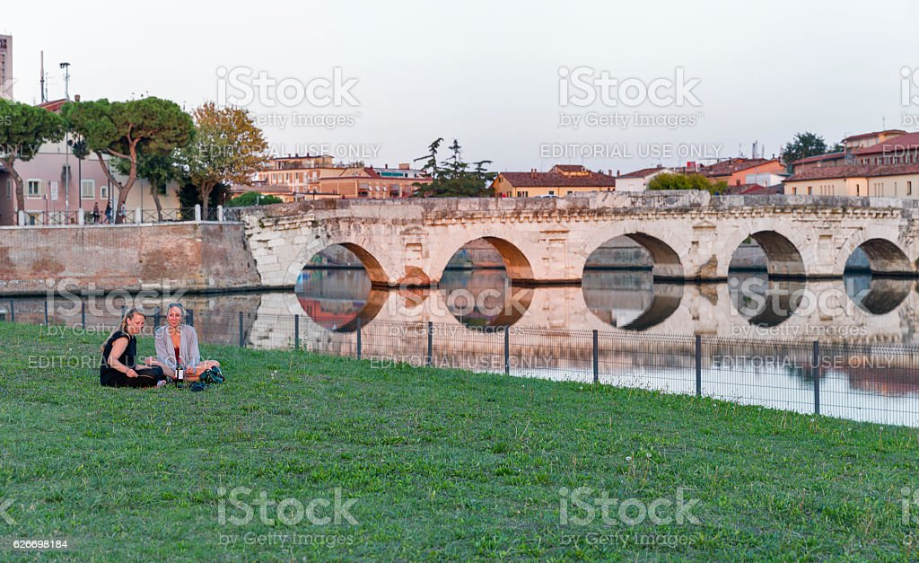 Woman sitting near the Tiberian bridge over the channel stock photo