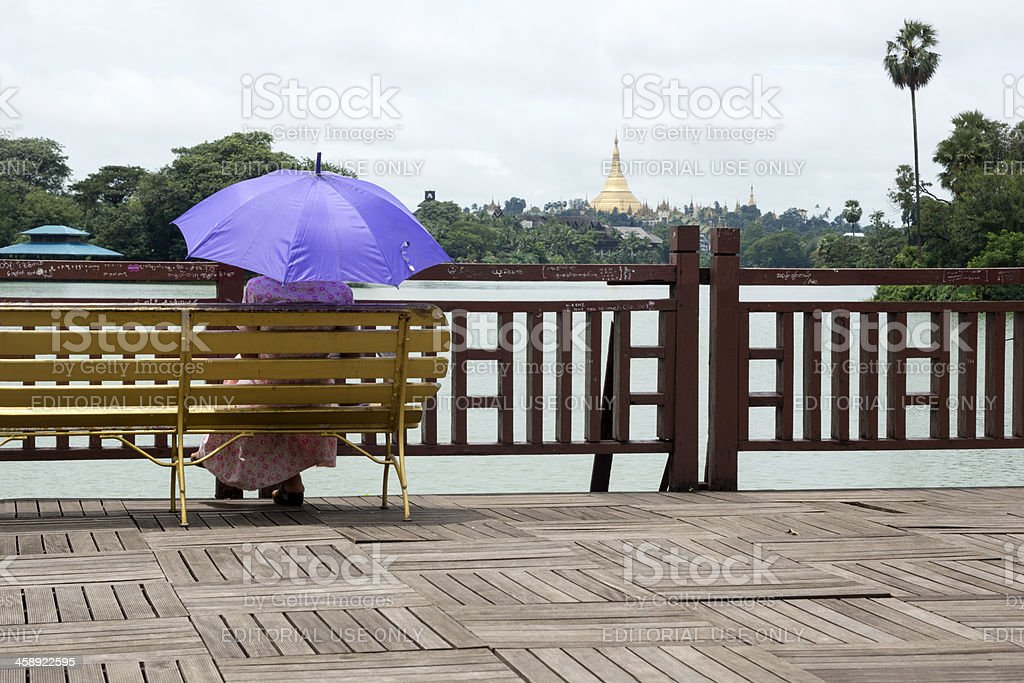Woman sitting on a bench and holding an umbrella stock photo