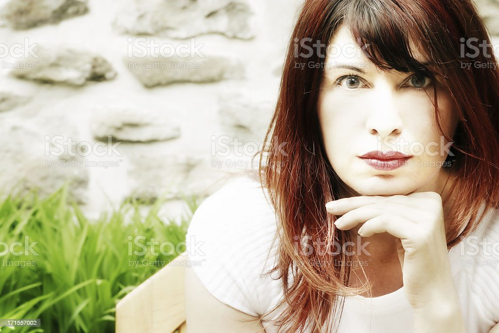 Woman Sitting on a Bench Listening royalty-free stock photo