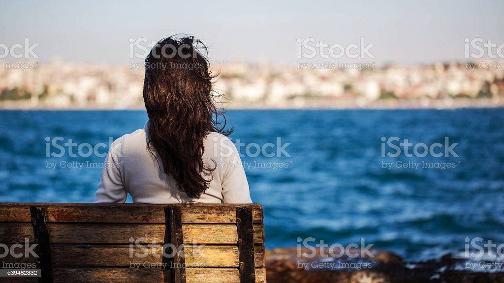 woman sitting on a bench looking at the Bosphorus view stock photo