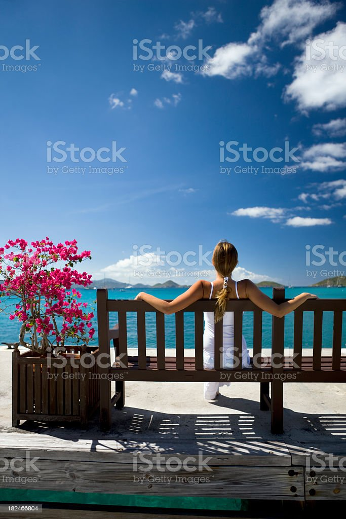 woman sitting on a bench looking at the Caribbean view royalty-free stock photo