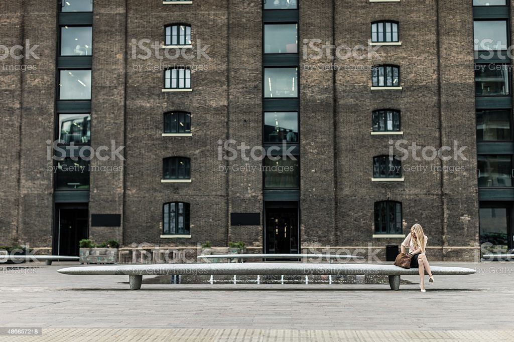 Woman sitting on a bench, searching in the bag stock photo