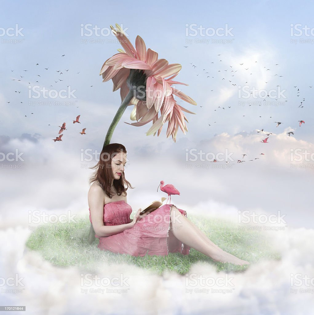 Woman sitting on a cloud with grass under a flower reading stock photo