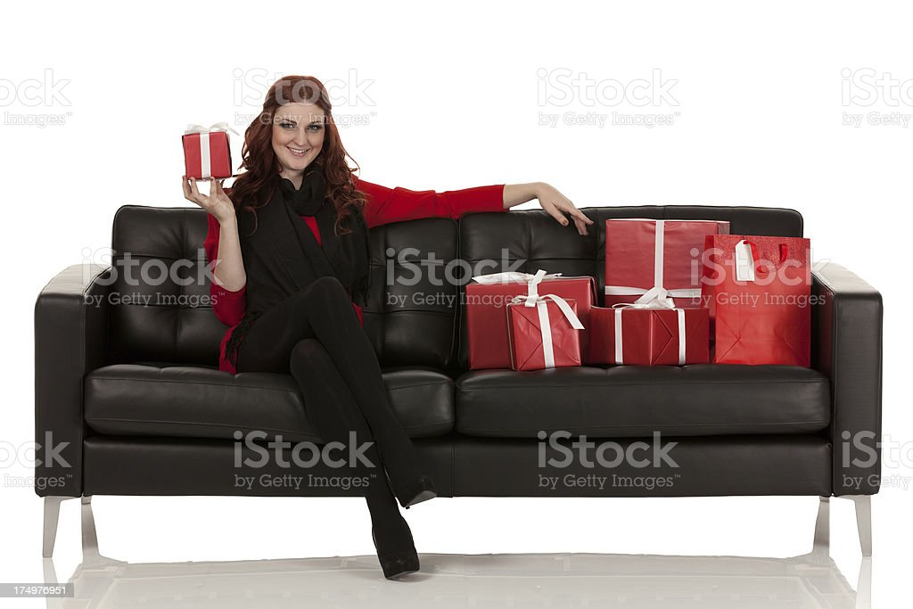 Woman sitting on a couch with Christmas gifts royalty-free stock photo