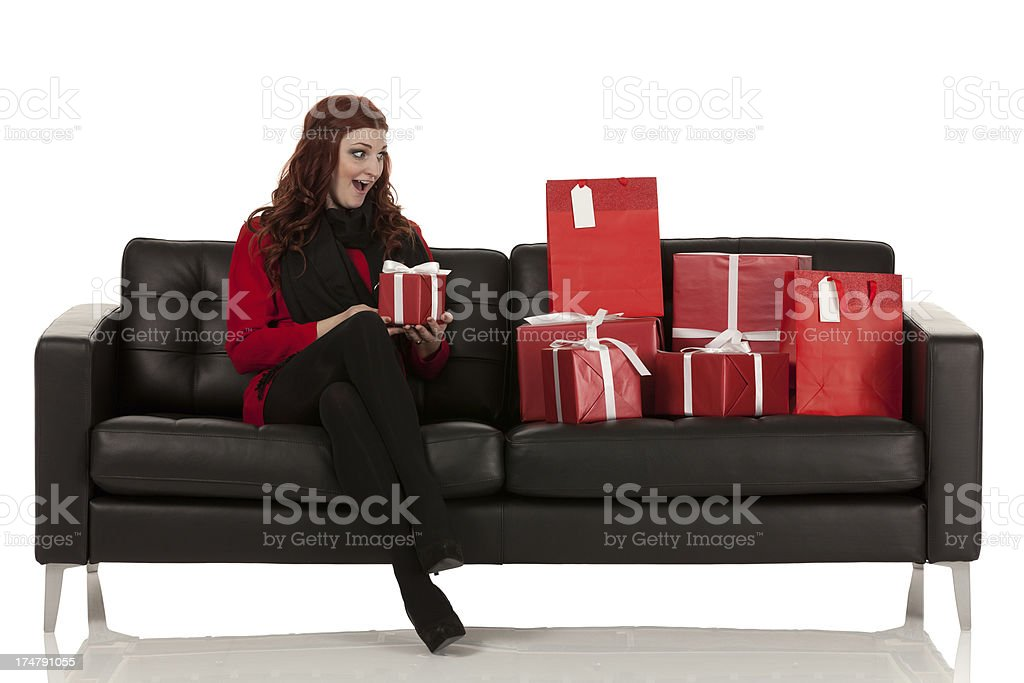 Woman sitting on a couch with Christmas presents royalty-free stock photo