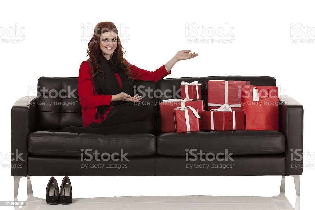 Woman sitting on a couch with presents royalty-free stock photo
