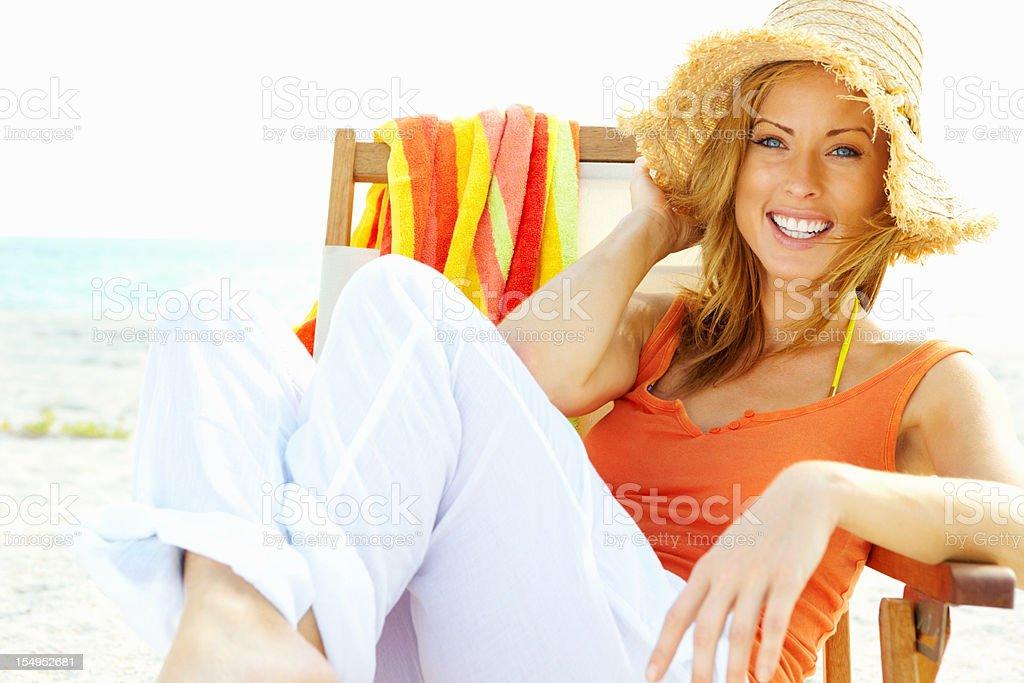 Woman sitting on a deck chair enjoying the beach royalty-free stock photo