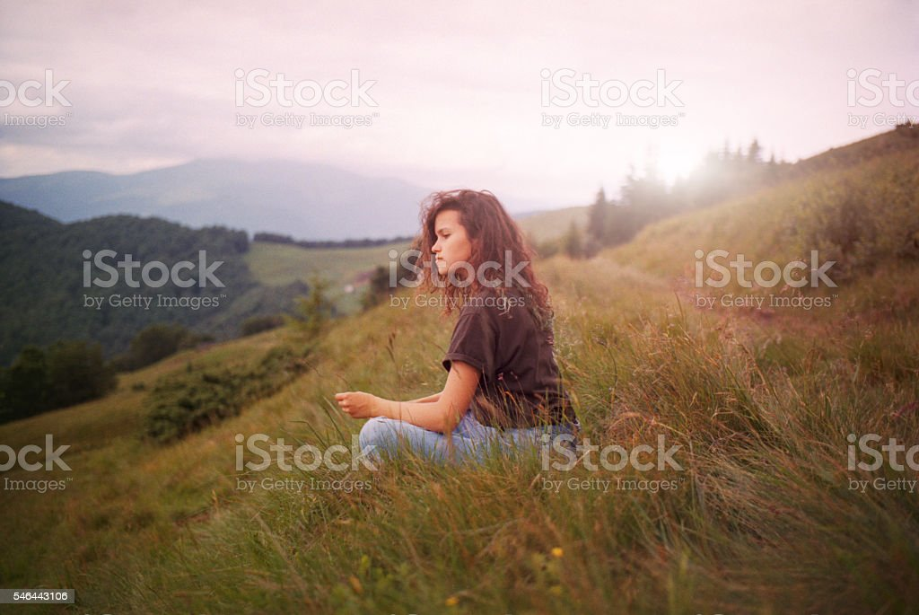 Woman sitting on a grass in the mountains stock photo