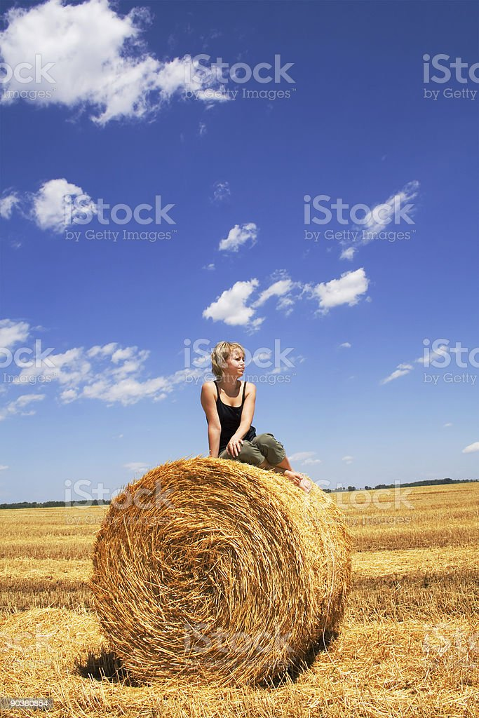 Woman sitting on a hay bale royalty-free stock photo