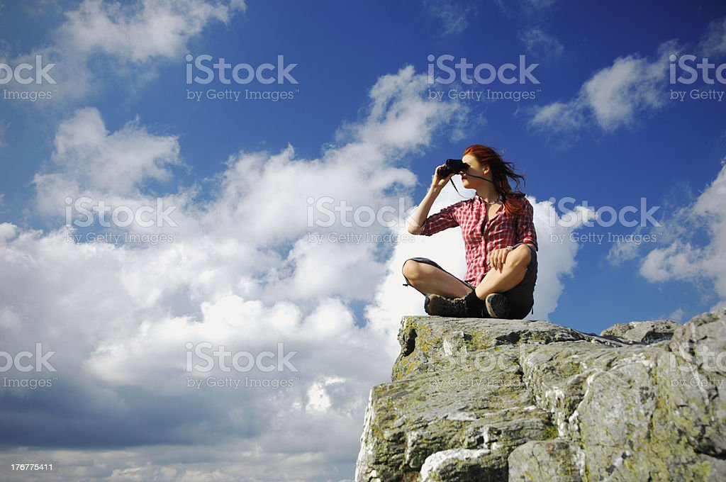 Woman sitting on a mountain with binocular stock photo