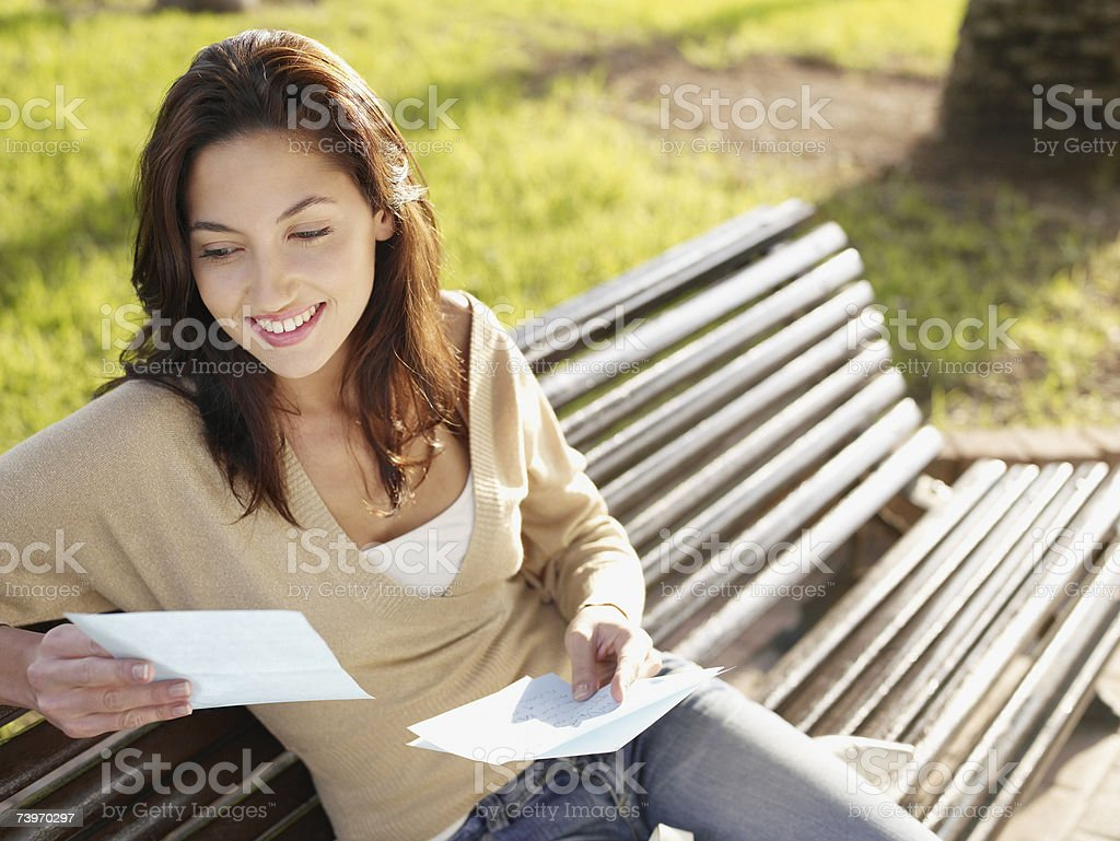 Woman sitting on a park bench reading a letter royalty-free stock photo