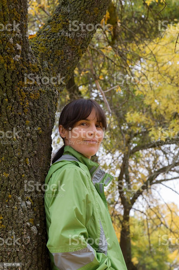 Woman sitting on a park bench with yellow leaves falling stock photo