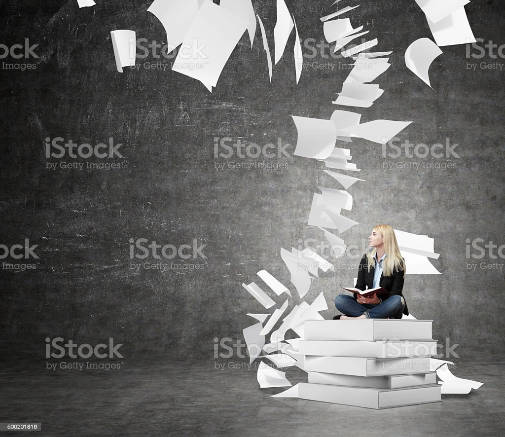 woman sitting on a pile of books thinking about problem stock photo
