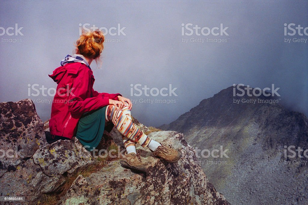 Woman sitting on a rock in the Rila mountains stock photo