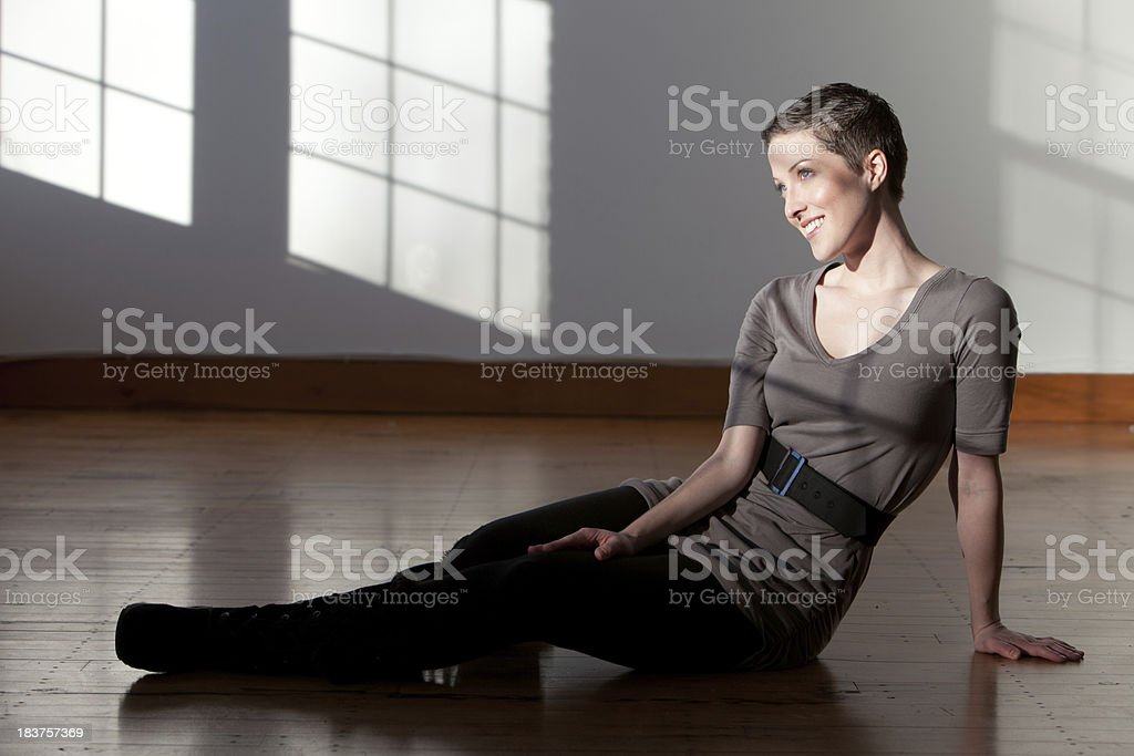 Woman sitting on a wooden floor stock photo
