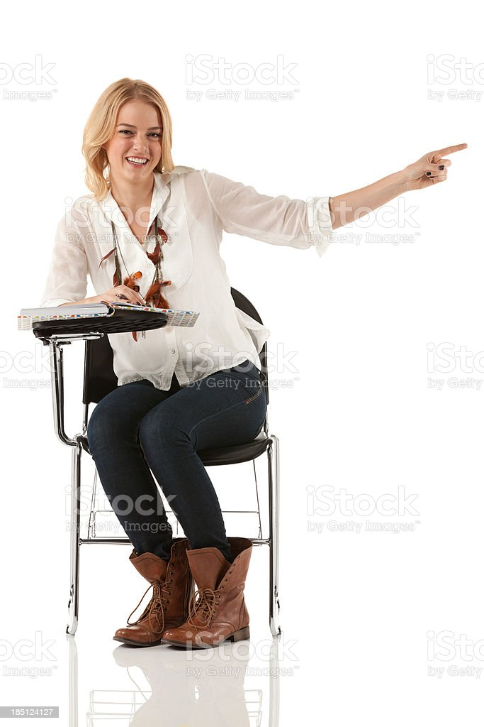 Woman sitting on a writing chair and pointing stock photo
