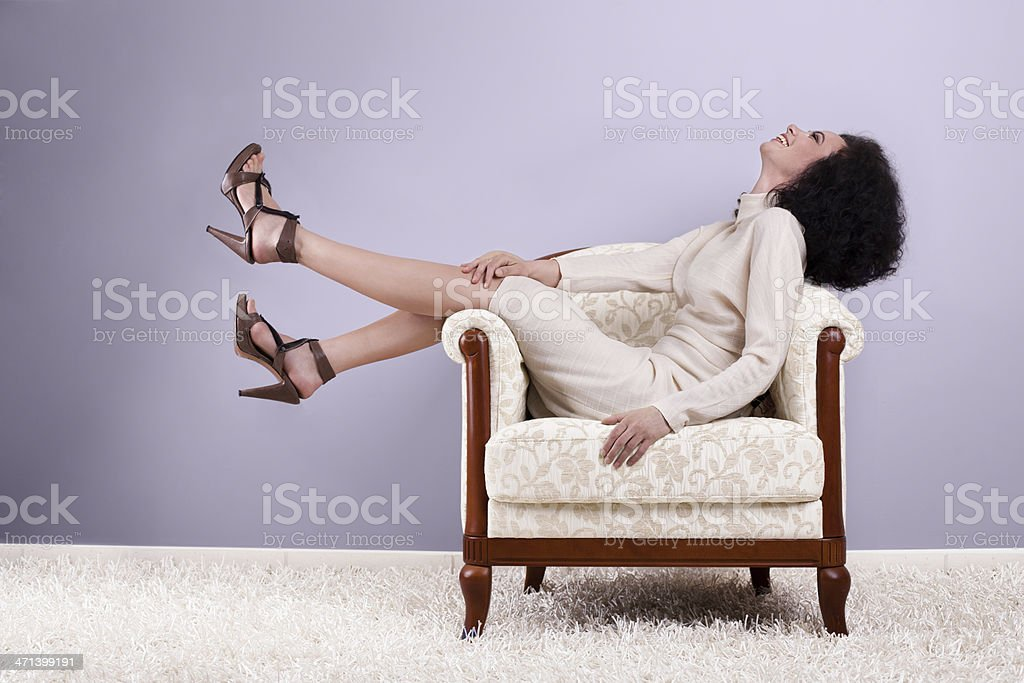 Woman sitting on armchair, profile, violet background stock photo