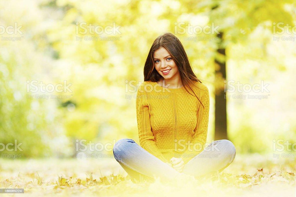 Woman sitting on autumn leaves royalty-free stock photo