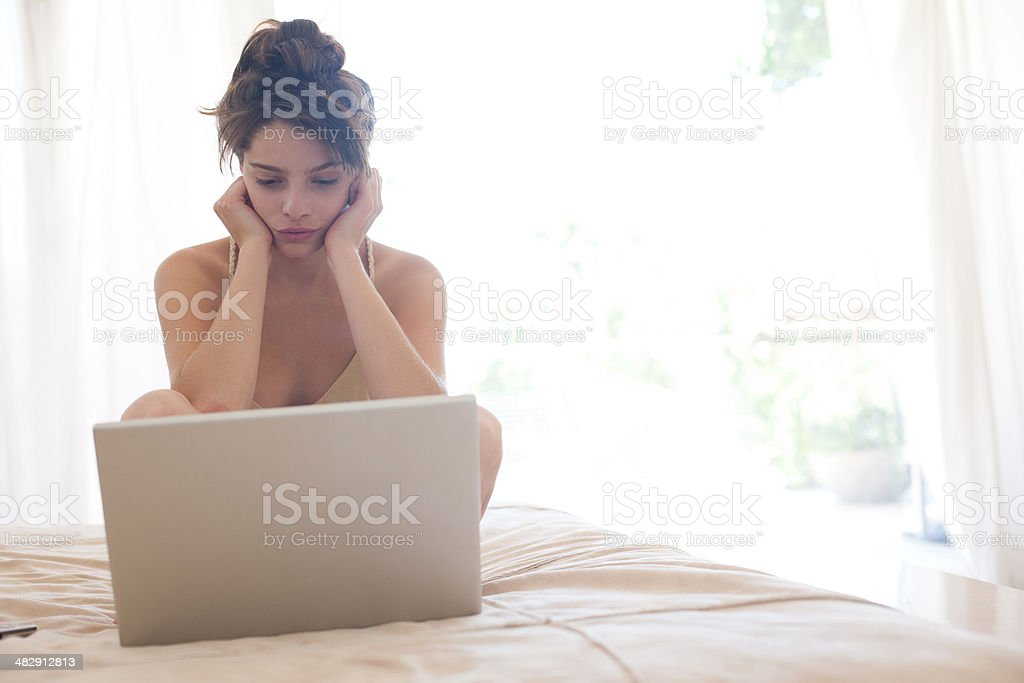 Woman sitting on bed looking laptop stock photo