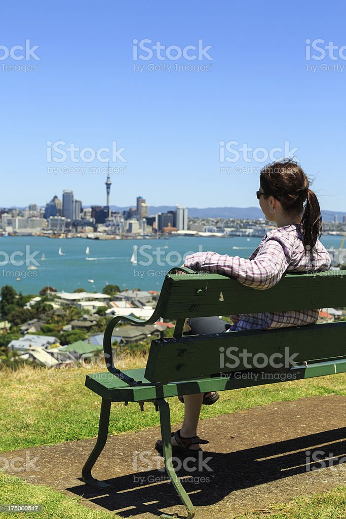 Woman Sitting on Bench and Looking at Auckland City royalty-free stock photo