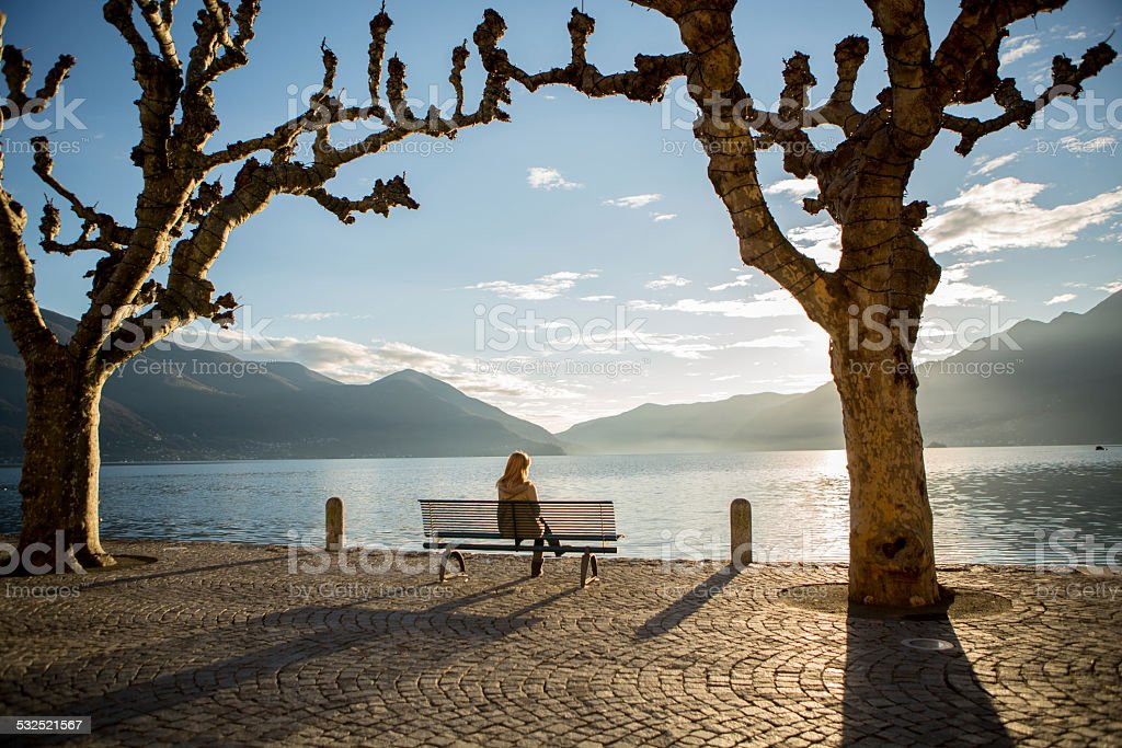 Woman sitting on bench near lake watching the sunset. stock photo