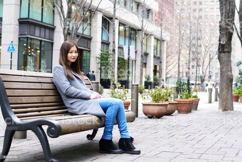 Woman sitting on bench stock photo