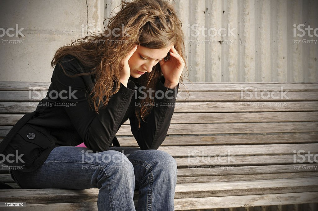 Woman sitting on bench with both hands on her temple royalty-free stock photo