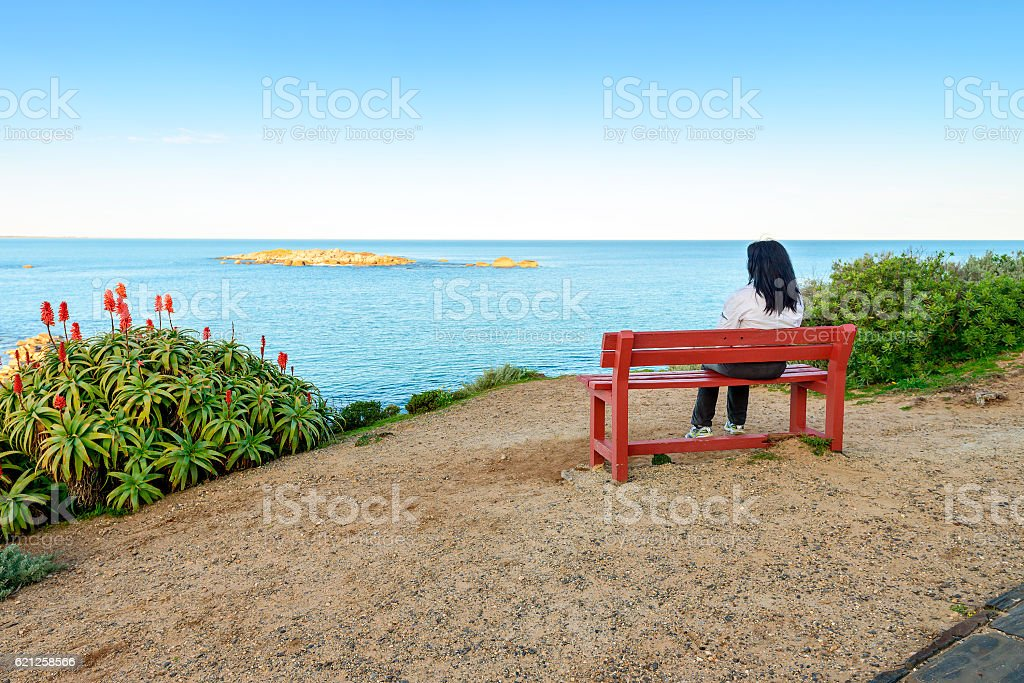 Woman sitting on bench with sea view stock photo