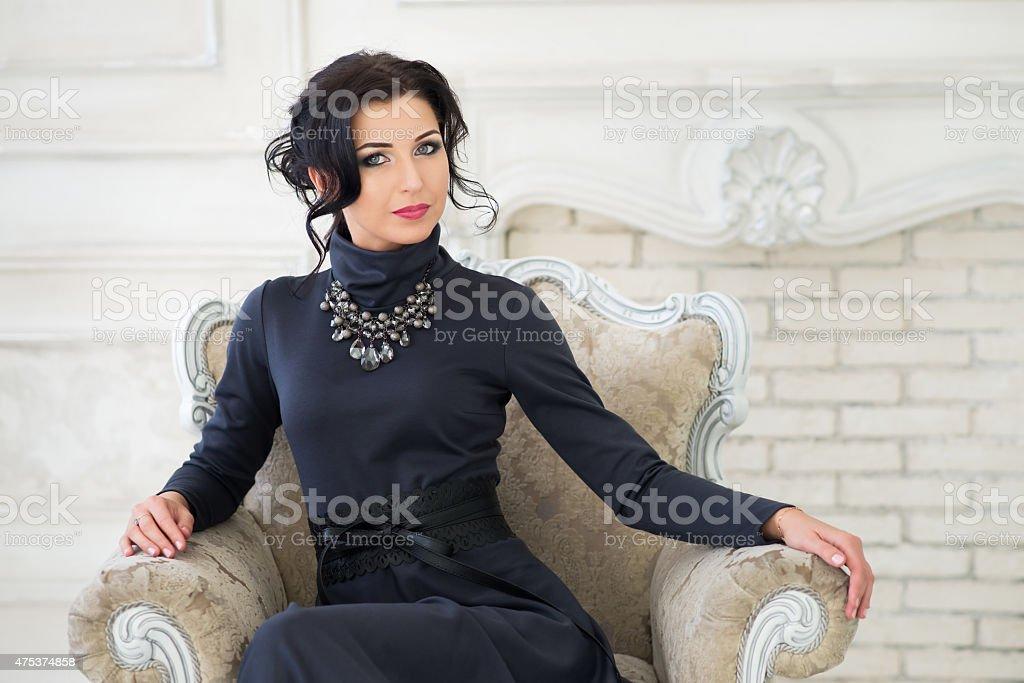 Woman sitting on chair. Luxury retro style. Vintage stock photo