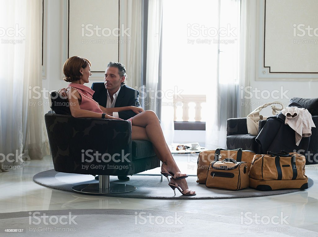 Woman sitting on chair with man beside looking at man stock photo