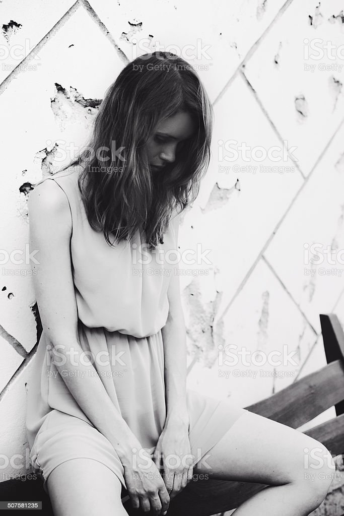 Woman sitting on concrete wall background stock photo