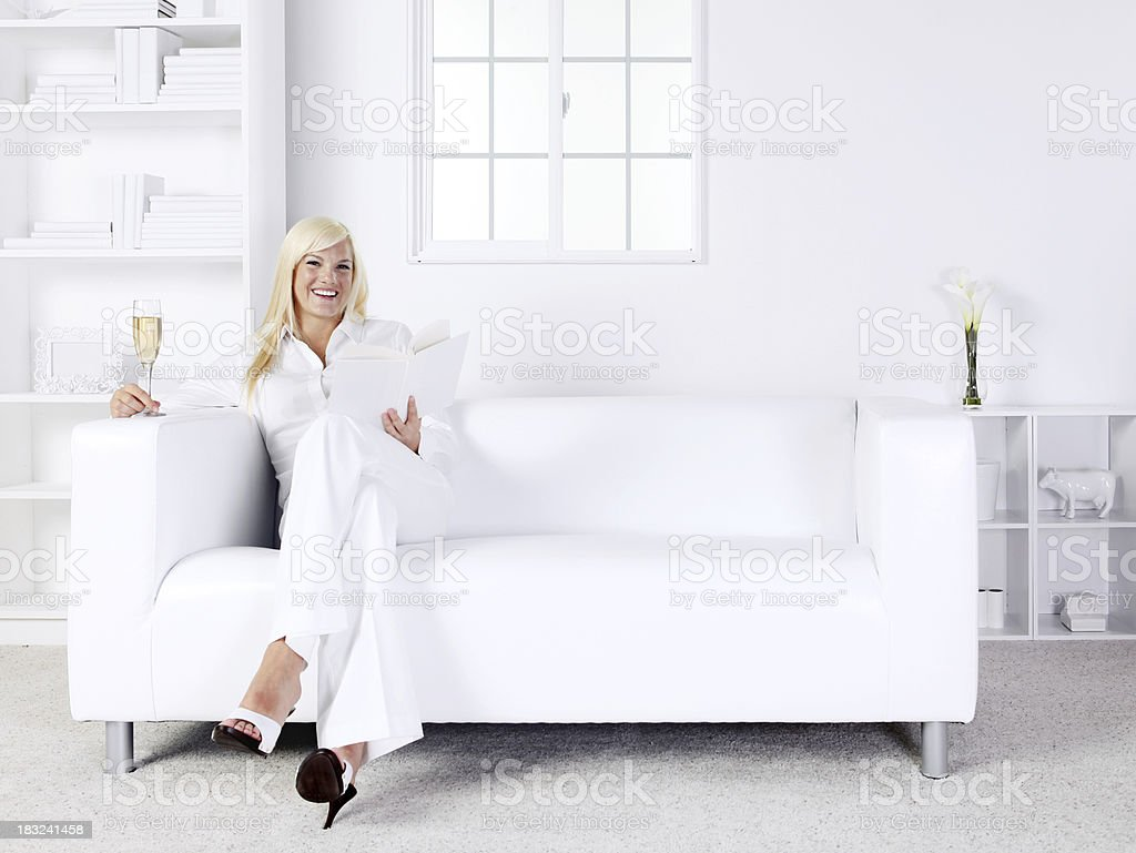 Woman sitting on couch holding champagne flute royalty-free stock photo