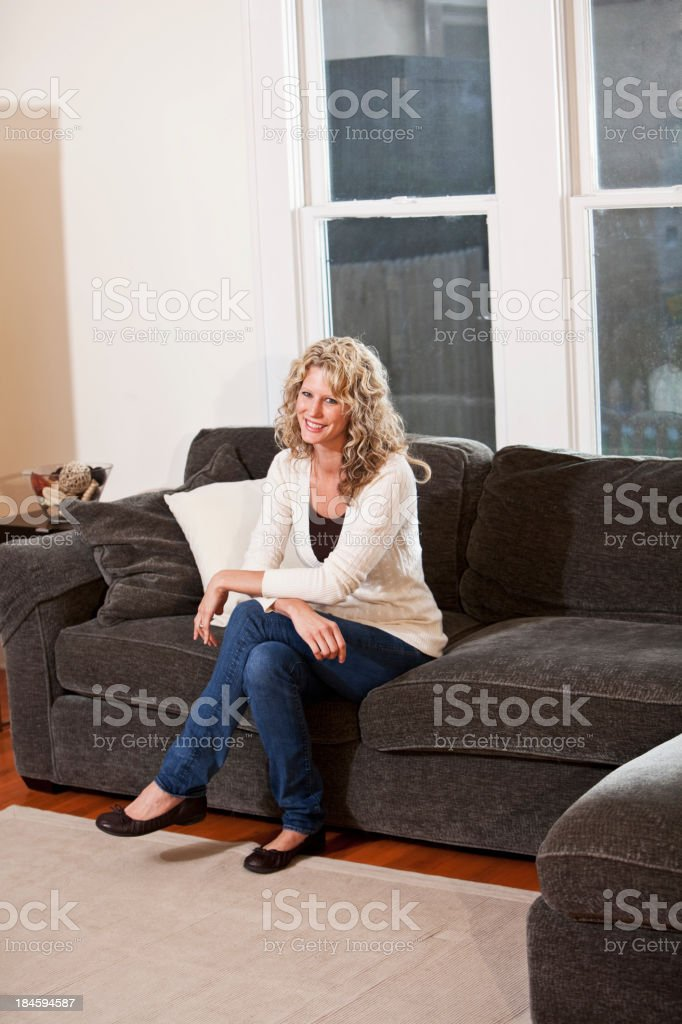 Woman sitting on couch in living room stock photo