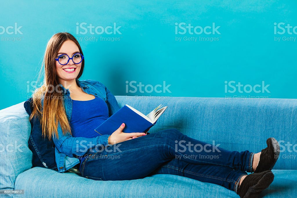 Woman sitting on couch reading book at home stock photo