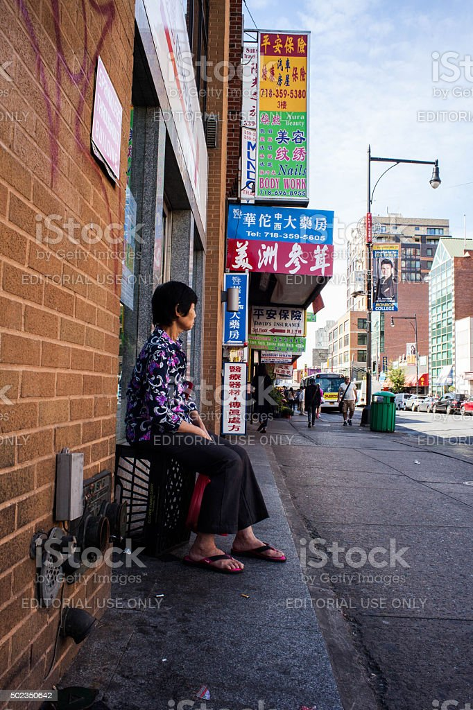 Woman Sitting on Crate in Flushing Queens' Chinatown stock photo
