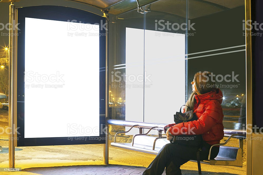 woman sitting on desk at bus stop stock photo