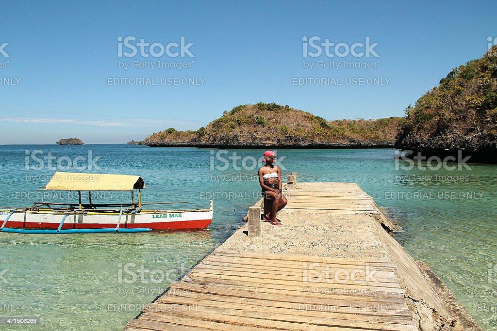 Donna seduta sul Dock in centinaia di isole, Filippine foto stock royalty-free