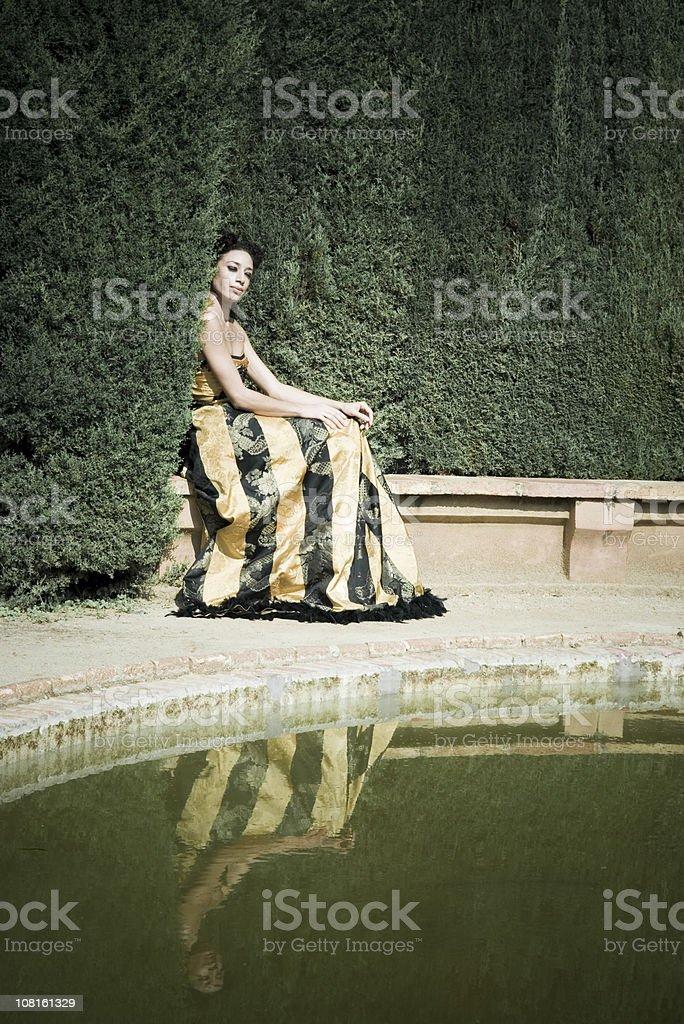 Woman Sitting on Edge of Garden Pond royalty-free stock photo