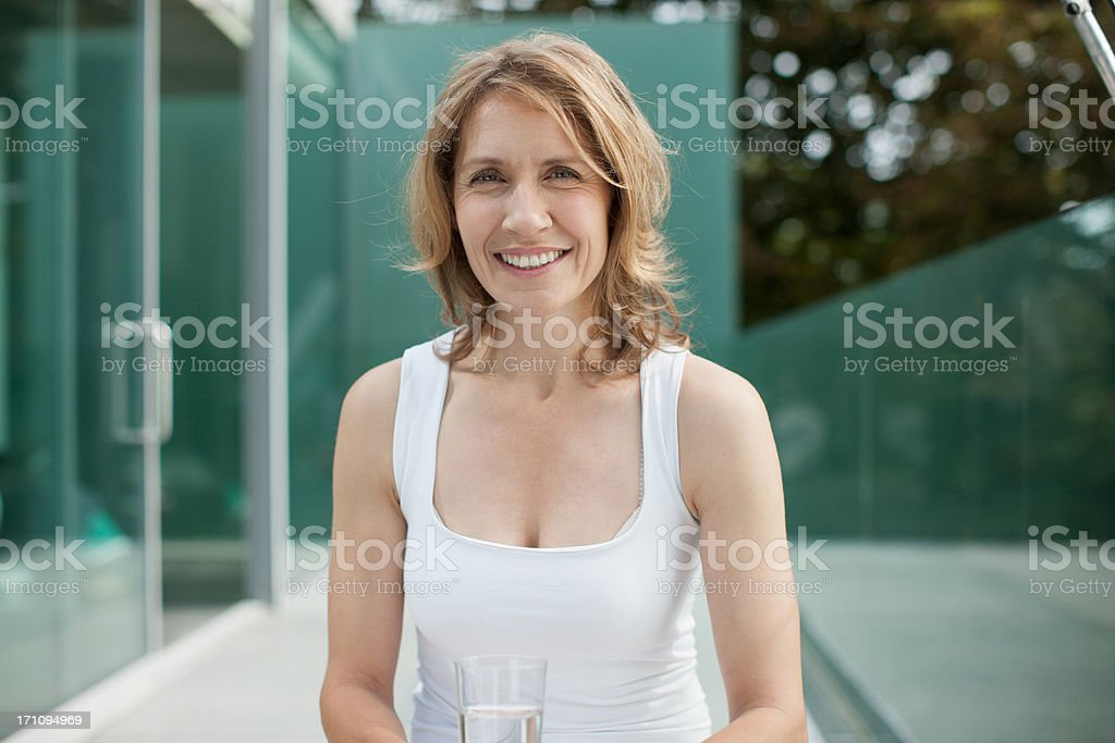 Woman sitting on exercise ball drinking water stock photo
