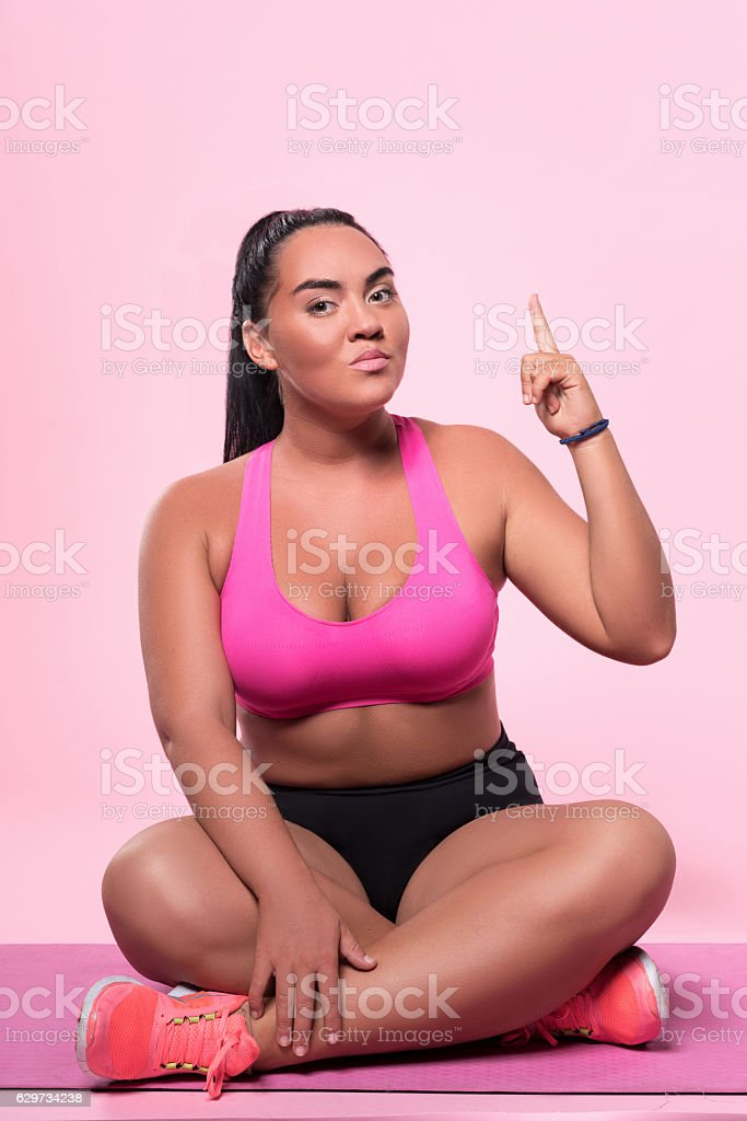 Woman sitting on floor and pointing up with index finger stock photo