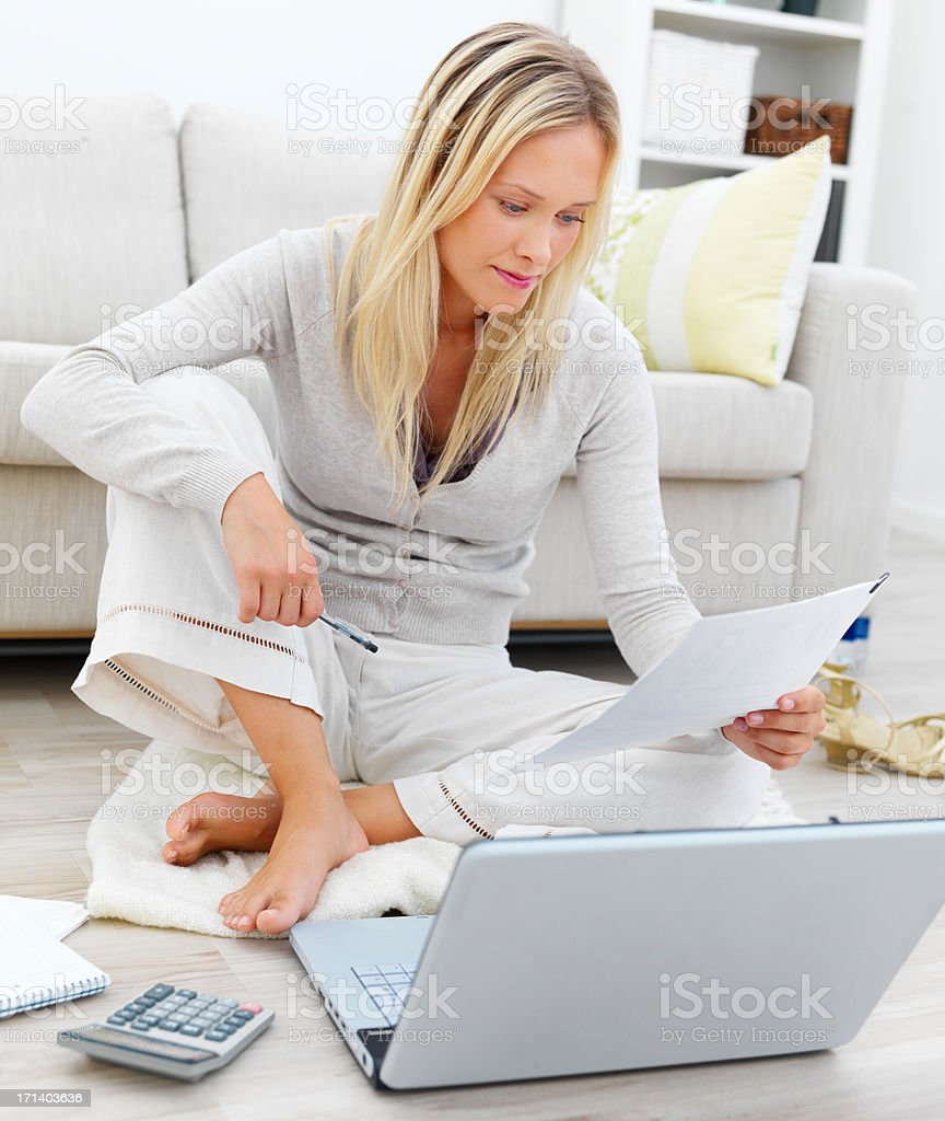 Woman sitting on floor and using laptop by sofa royalty-free stock photo